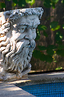 A pool side decoration, a sculpture of a man's face with a profusion of hair and beard and moustache, in afternoon warm sunshine in Provence Clos des Iles Le Brusc Six Fours Cote d'Azur Var France