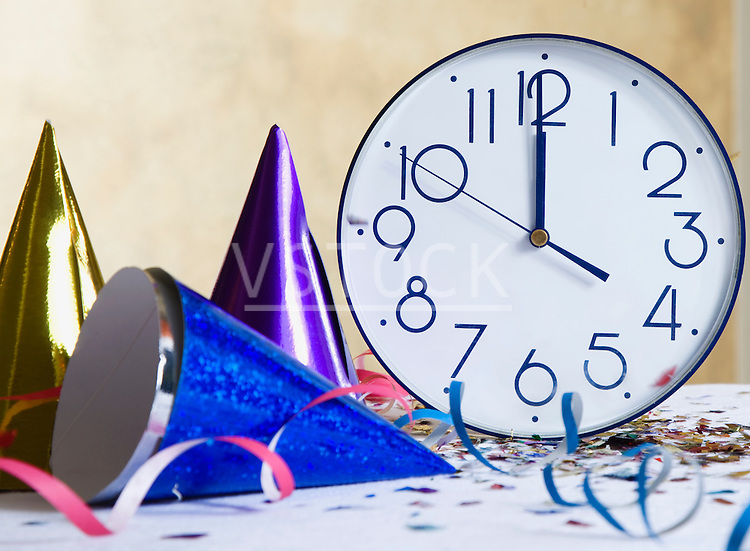 New Year's party hats, streamers next to clock showing midnight