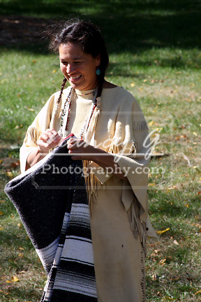 A Native American Indian woman folding a blanket