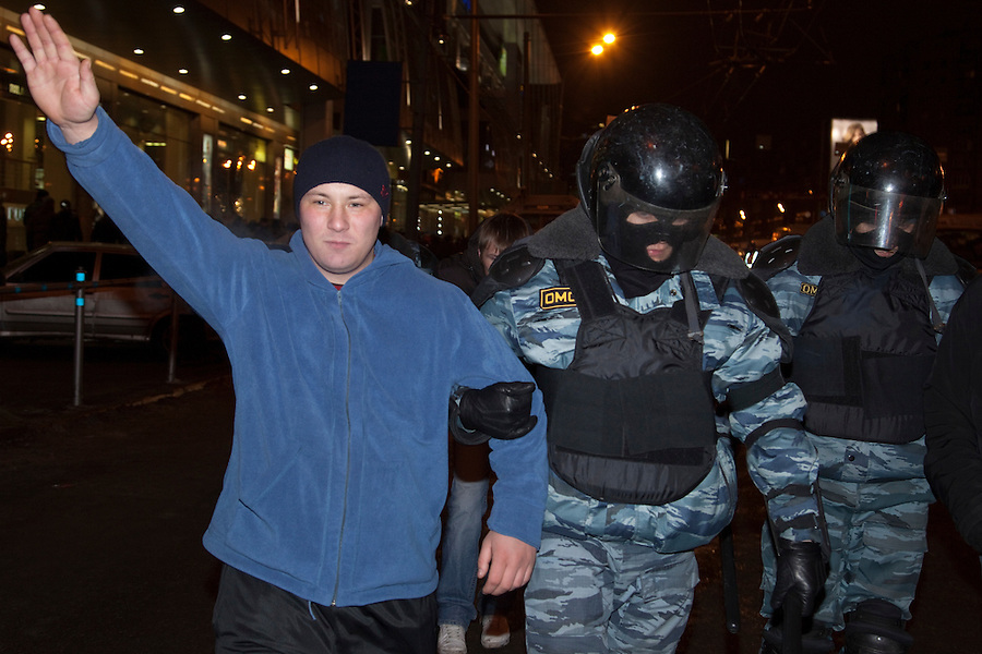 Moscow, Russia, 15/12//2010..A Russian nationalist youth makes a fascist salute as he is arrested by masked riot police near Kievsky railway station, where police detained up 1,000 people during an operation to prevent ethnic riots. There were scuffles as hundreds of riot police were deployed to prevent clashes between Russian nationalists and traders from the Caucasus, many of whom work at a market near the station.