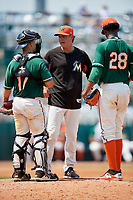 Greensboro Grasshoppers pitching coach Mark DiFelice (center) talks with catcher Michael Hernandez (17) and starting pitcher Edward Cabrera (28) during a game against the Lakewood BlueClaws on June 10, 2018 at First National Bank Field in Greensboro, North Carolina.  Lakewood defeated Greensboro 2-0.  (Mike Janes/Four Seam Images)