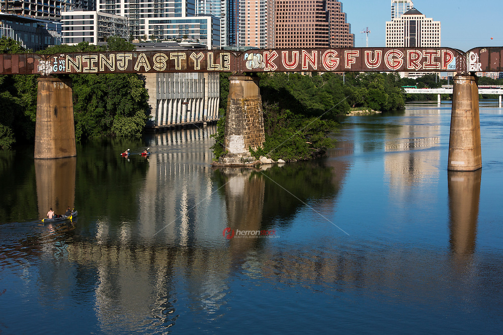 """The Austin Railroad Graffiti Bridge over Lady Bird Town Lake is Austin's official beloved and favorite series of graffiti paintings showcasing inspired artwork tag-lines """"I've got Ninja Style Kung Fu Grip"""" by mysterious artist SKO - Stock Image."""