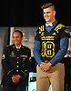 Jeremy Ruckert, Lindenhurst High School senior, dons the jersey he was presented with after officially being named a US Army All-American at the school on Monday, Oct. 2, 2017. Standing alongside him is Staff Sergeant Sarah Marrero.