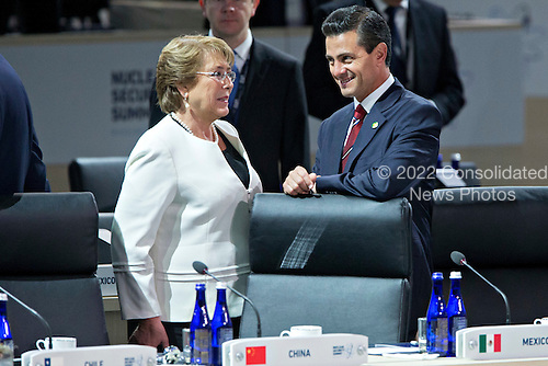 """Enrique Pena Nieto, Mexico's president, right, talks to Michelle Bachelet, Chile's president, during an opening plenary entitled """"National Actions to Enhance Nuclear Security"""" at the Nuclear Security Summit in Washington, D.C., U.S., on Friday, April 1, 2016. After a spate of terrorist attacks from Europe to Africa, U.S. President Barack Obama is rallying international support during the summit for an effort to keep Islamic State and similar groups from obtaining nuclear material and other weapons of mass destruction. <br /> Credit: Andrew Harrer / Pool via CNP"""