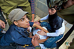 An Israeli peace activist argues with an Israeli soldier as she tries to protect an injured fellow activist from the soldiers in the village of An Nabi Salih near Ramallah on 11/06/2010. The injured man had tried to prevent a fight between the soldiers & two Palestinian women & was knocked to the ground by a soldier who subsequently kicked him as he lay injured.