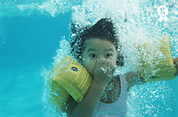 Girl (8-10) in swimming pool, holding nose underwater, close-up (Licence this image exclusively with Getty: http://www.gettyimages.com/detail/200387439-001 )