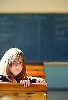 A young girl sits in an old-fashioned classroom.