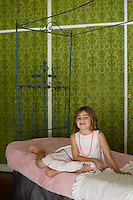 In Aurora's bedroom wallpaper in a pretty green floral design and an antique wrought-iron bed with a pale pink cover create a bright and fresh feel