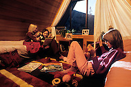 Wasco, Oregon, January 1984: A family at home in Rajneeshpuram. Swami Antar Svargo, 33 yrs, Ma Deva Shantam, 35 yrs and Ma Dhyan Deepta, 9 yrs. Settled in Rajneeshpuram in May 1982. Rajneeshpuram, was an intentional community in Wasco County, Oregon, briefly incorporated as a city in the 1980s, which was populated with followers of the spiritual teacher Osho, then known as Bhagwan Shree Rajneesh. The community was developed by turning a ranch from an empty rural property into a city complete with typical urban infrastructure, with population of about 7000 followers.