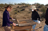 Mareen Hopkins (left).a university of arizona student works with Tomoko Mochihara, a university of Hawaii student,.screen dirt from.the Marana Platform mound looking for.shards and other artifacts from the .mound occupied for 100 years by the HoHoKam.people from 1200 ad to 1300 ad...