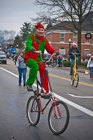 Riding an oversize bike and wearing an elf costume a man entertains the kids waiting to Santa at the end of  the Westerville Christmas Parade