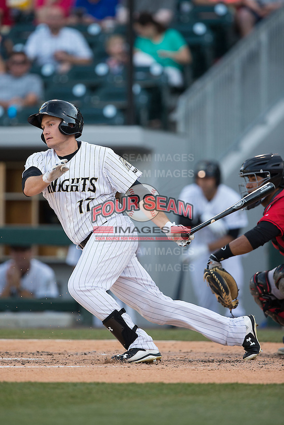 Jason Coats (17) of the Charlotte Knights follows through on his swing against the Indianapolis Indians at BB&T BallPark on June 20, 2015 in Charlotte, North Carolina.  The Knights defeated the Indians 6-5 in 12 innings.  (Brian Westerholt/Four Seam Images)