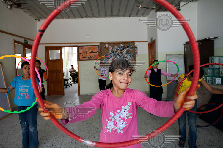 Girls exercise with hoops during a class at the Nour El Marifa School for Special Needs.
