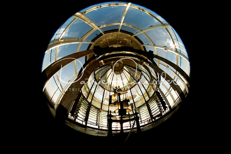 The Currituck Beach Lighthouse, one of the few North Carolina coastal lighthouses that visitors can climb to the top, is located on the Outer Banks in Corolla, North Carolina. Photo taken with an 8mm circular fisheye lens. With its red brick exterior, the lighthouse is  an example of Gothic Revival architecture. Located in the town of Corolla, the Currituck Beach Light was the last of four beacons placed at intervals from Cape Henry, Virginia to Cape Hatteras. Like other lighthouses on the North Carolina coast, the Corolla Lighthouse / Currituck Beach Lighthouse still aids ships in navigation. Charlotte NC photographer Patrick Schneider has extensive photo collections of the following lighthouses: Bodie Island Lighthouse, Bald Head Island Lighthouse, Cape Fear Lighthouse, Cape Hatteras Lighthouse, Cape Lookout Lighthouse, Currituck Beach Lighthouse, Diamond Shoal Lighthouse, Federal Point Lighthouse, Oak Island Lighthouse, and Ocracoke Lighthouse on Ocracoke Island.