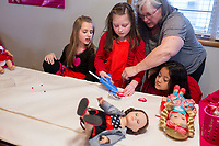NWA Democrat-Gazette/CHARLIE KAIJO Pat Glisson (right) helps Kiera Billing, 9, of Bentonville (center) with crafts while Kelsey Fisher, 9, of Bentonville (left) and Charlotte Roat, 5, of Bentonville (bottom right) watch, Sunday, February 11, 2018 at the Croppin' Train Hobby House in Bentonville. <br /><br />Girls brought their 18&quot; dolls to a Girls &amp; Dolls Valentine Party. The girls enjoyed a light luncheon, then some crafting for themselves and their dolls.<br /><br />Typically adult women will come to Hobby House and stay for a weekend retreat and scrapbook. The house provides beds for the women interested in staying for the weekend. They provide women a chance to get together and fellowship.