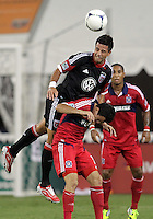 WASHINGTON, DC. - AUGUST 22, 2012:  Marcelo Saragosa (11) of DC United heads the ball over  Marco Pappa (16)of the Chicago Fire during an MLS match at RFK Stadium, in Washington DC,  on August 22. United won 4-2.