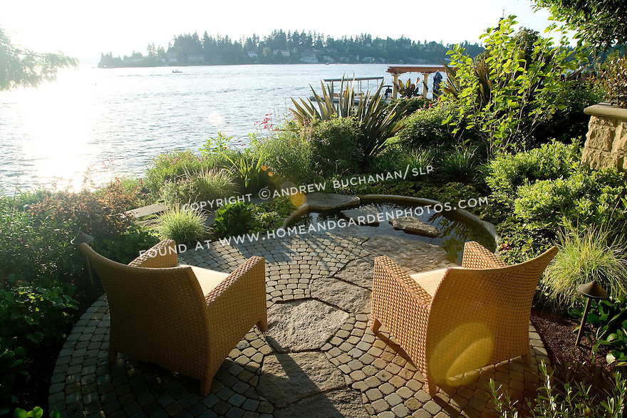 a sun flare highlights two chairs sitting in the late afternoon summer sunshine on a small, private, waterfront patio tucked in the side of a grand estate garden