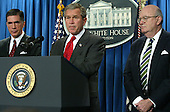United States President George W. Bush pauses while speaking to the media as former Virginia governor and U.S. Senator Chuck Robb (Democrat of Virginia), left, and Judge Laurence Silberman, right, listen February 6, 2004 in the briefing room of the White House in Washington, DC. President Bush appointed Robb and Silberman to head a bipartisan commission that will investigate the Iraqi intelligence failures. <br /> Credit: Alex Wong / Pool via CNP