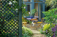 Painted garden chairs around a small table have been placed on a paved patio infront of the conservatory