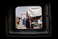 ABU GHRAIB, IRAQ - JULY 9: Iraqi civilians stare at a passing American Army Humvee as the unit patrols a commerical district of Abu Ghraib on July 9 2007. The level of violence in Iraq is so high that the only way for foreigners and soldiers to observe civilian life is through the relative safety of an armored vehicle window. (Photo by Benjamin Lowy/Reportage by Getty Images)
