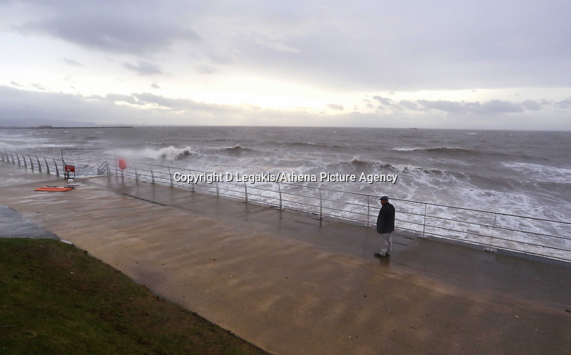 WEATHER PICTURE SWANSEA<br /> Pictured: A lone man walking as the waves crashing against the Swansea seafront wall, south Wales. Monday 03 February 2014<br /> Re: High tides combined with strong winds are affecting parts of the UK.