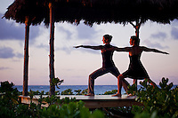 Women practicing yoga postures in a beachfront gazebo