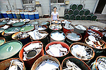 Sonae Fujii of the Zero Waste Academy in Kamikatsu stands next to containers filled with waste ready for recycling at the Hibigaya Waste Station in central Kamikatsu Town in Shikoku, Japan. The town, whose residents number just over 2,000 people, has implemented a waste recycling policy that aims at eliminating waste entirely within the next 12 years and employs retired local residents to care for the waste disposal center. Waste must be divided up into 34 categories.  .Photographer: Robert Gilhooly