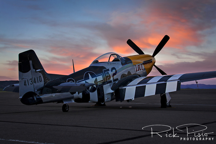 "P-51 Mustang ""Lou IV"" sits on the ramp Stead Field at sunset."
