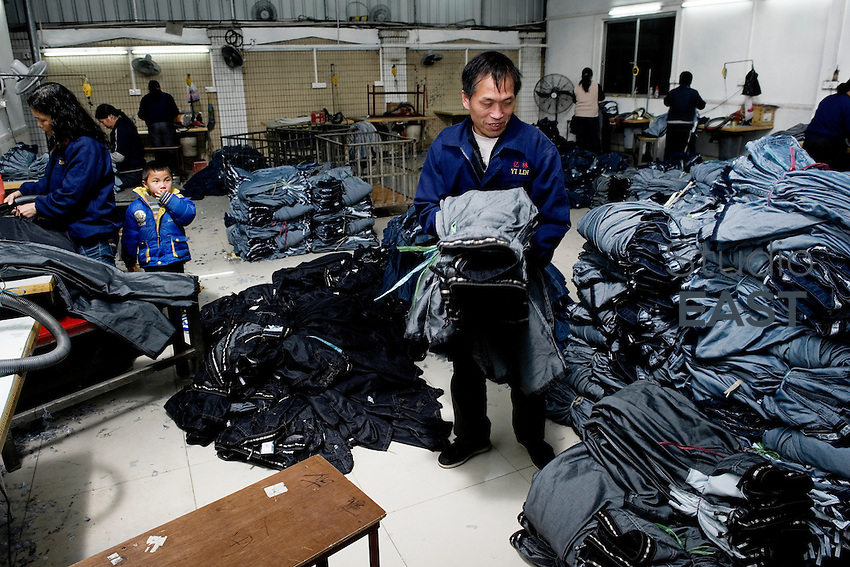 Workers, sometimes accompanied by their children, manufacture blue jeans in Yilin textile factory in Dongguan, Guangdong province, China, on February 10, 2012. Photo by Lucas Schifres/Pictobank