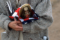 Stella Garcia, 67, of Edgewood, N.M., carries a Virgen de Guadalupe statue wrapped in an American flag enroute to the Santuário de Chimayó in northern New Mexico on Good Friday. Thousands of pilgrims make a pilgrimage to the 190-year-old shrine every Easter as an expression of faith, a connection to old Hispanic roots and in hopes of the miracles reputed to occur there.<br />