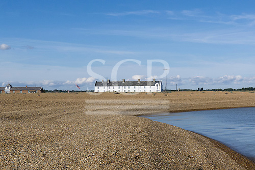 Shingle Street, Suffolk. Row of whte coastguard cottages with a Union Jack flag, shingle beach, sea.