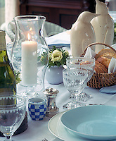 Two white china penguins stand guard over a table laid for lunch with plain blue and white china