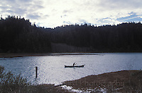 A person paddling a canoe up Big River, Mendocino California