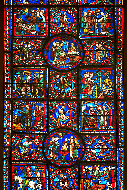 Medieval Windows of the Gothic Cathedral of Chartres, France, dedicated to St Martin of Tour.    A UNESCO World Heritage Site. In the top central oval panel St Martin is ordained Bishop of Tour, box below left Martin is attacked by brigands. Bottom central oval panel shows Martin being baptised.