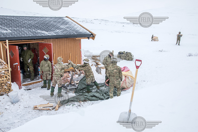 Soldiers carry firewood dropped off by helicopter. The newly built Vouma cabin in Dividalen National Park is part of the Norwegian Trekking Association network. As a goodwill gesture and part of their Arctic training the Royal Navy use helicopters to fly firewood to the remote location. <br /> <br /> <br /> In 2019 the Arctic exercise Clockwork passed 50 years of training in Norway, and now has a permanent base within the Norwegian Air Force base at Bardufoss. <br /> <br /> 845 Naval Air Squadron is a squadron of the Royal Navy's Fleet Air Arm. Part of the Commando Helicopter Force, it is a specialist amphibious unit operating the Leonardo Commando Merlin Mk3 helicopter and provides troop transport and load lifting support to 3 Commando Brigade Royal Marines.<br /> <br /> ©Fredrik Naumann/Felix Features