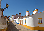 Traditional architecture with large chimneys in  whitewashed houses and street in the small rural settlement village of Terena, Alentejo Central, Portugal, Southern Europe