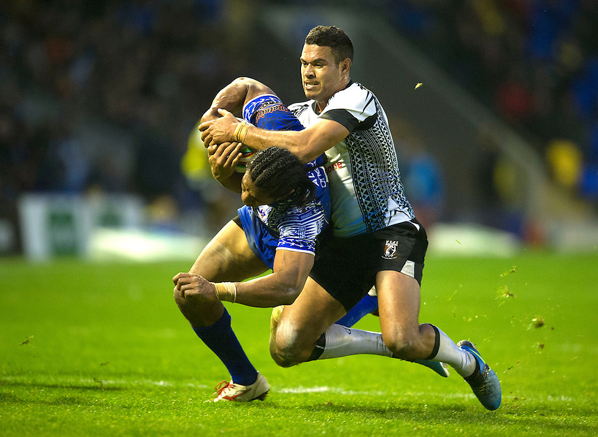 Samoa's Iosia Soliola holds off the challenge from Fiji's Daryl Millard <br /> <br /> Photo by Stephen White/CameraSport<br /> <br /> 2013 Rugby League World Cup - Quarter Final - Samoa v Fiji - Sunday 17th November 2013 - Halliwell Jones Stadium - Warrington<br /> <br /> &copy; CameraSport - 43 Linden Ave. Countesthorpe. Leicester. England. LE8 5PG - Tel: +44 (0) 116 277 4147 - admin@camerasport.com - www.camerasport.com