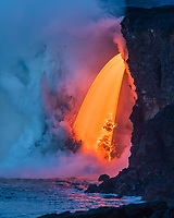 "Lava Fall: A fire hose of lava or ""lava fall"" at the Kamokuna ocean entry for Kilauea Volcano, Big Island. This is by far the most volume and fastest amount of lava a fire hose (or lava hose) has produced in recorded history. Photo taken at the ""Blue Hour"" (transition of dawn light into daylight), January 29, 2017."