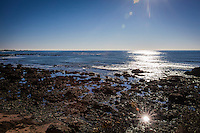 A sun burst gleams from the rocky shoreline along the Whitehouse Creek Trail at Año Nuevo State Reserve on New Year's Day, 2015.