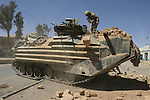 AR RUTBAH, Iraq- A Marine from Alpha Company, 4th Amphibious Assault Vehicle (AAV) Battalion removes rubble from the top of his AAV after it was used to knock down a wall. The Marines of Regimental Combat Team 2 conduct counter-insurgency operations with Iraqi Security Forces to isolate and neutralize anti-Iraqi forces, to support the continued development of Iraqi Security Forces, and to support Iraqi reconstruction and democratic elections in order to create a secure environment that enables Iraqi self-reliance and self-governance. (Official USMC photo by Lance Cpl. Shane S. Keller)
