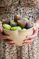 A simple bowl filled with freshly picked figs in the hands of Italian chef Maddalena Caruso