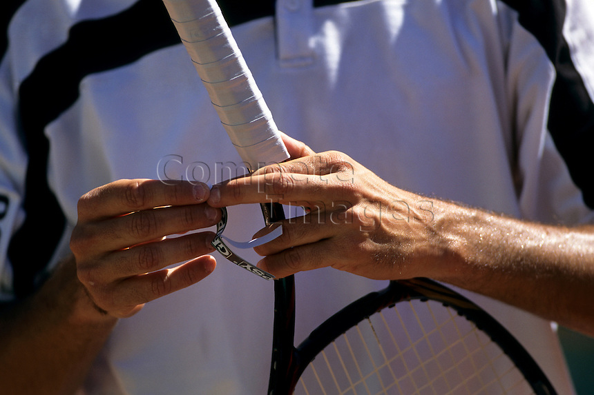 Tennis player applying grip tape to his tennis racquet