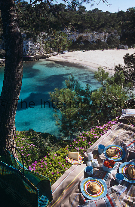 A picnic is laid out on a striped tablecloth under a tree overlooking an empty beach on the island of Majorca