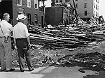 His sagging shoulders and drooping hands reflected the dismay with which Gov. Abraham Ribicoff surveyed the Naugatuck River flood damage yesterday with Mayor Raymond E. Snyder, left. The Governor toured devastated local areas with officials and newsmen. This view is from Riverside Street looking toward the Brooklyn Bridge.22 August 1955