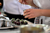 Melbourne, 30 May 2017 - Laura Skvor commis chef assisting Michael Cole of the Georgie Bass Cafe & Cookery in Flinders works on a garnish at the Australian selection trials of the Bocuse d'Or culinary competition held during the Food Service Australia show at the Royal Exhibition Building in Melbourne, Australia. Photo Sydney Low