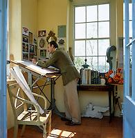 Portrait of furniture designer Thomas Messel drawing in his summer studio