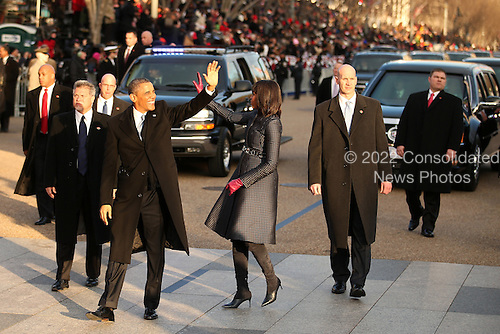 United States President Barack Obama and First Lady Michelle Obama wave to onlookers as the presidential inaugural parade winds through the nation's capital January 21, 2013 in Washington, DC. Barack Obama was re-elected for a second term as President of the United States.  .Credit: Chip Somodevilla / Pool via CNP