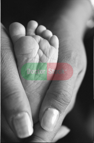 mother's thumbs around newborn baby foot