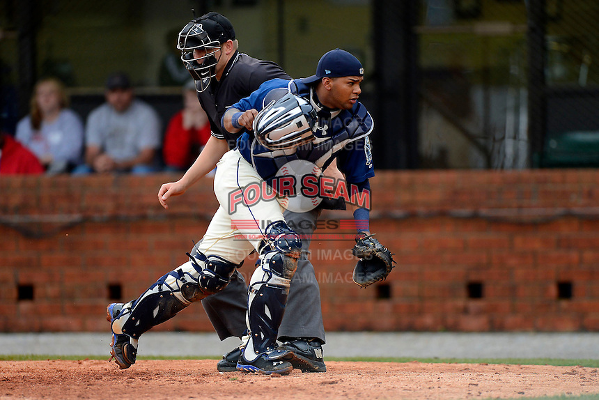 Mobile BayBears catcher Rossmel Perez #14 looks for a passed ball in front of umpire Brandon Henson during a game against the Pensacola Blue Wahoos on April 14, 2013 at Hank Aaron Stadium in Mobile, Alabama.  Mobile defeated Pensacola 5-2.  (Mike Janes/Four Seam Images)