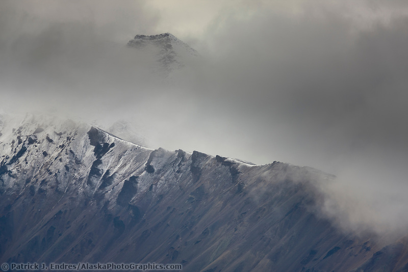 Clouds obscure a light snow that highlights a rocky mountain ridge in the Alaska Range mountains of Denali National Park, Interior, Alaska.